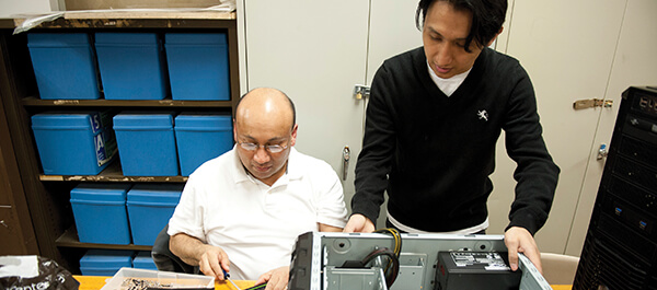 Student and Faculty working on fixing a computer together